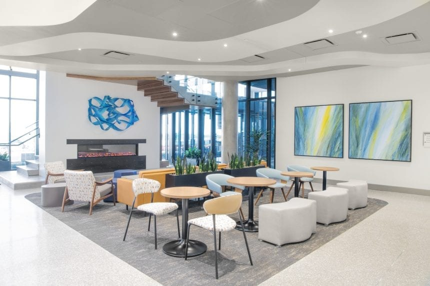 Blue is being used as a signature color - a contemporary pop of color in a mostly neutral palette of the interiors. The blue ribbon sculpture is by commissioned artist Renee Dinauer and the painting is by Michael Ireland.