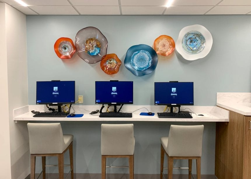 Houston Methodist Willowbrook - Dining Area. Hand-crafted art glass installation that coordinates with the colors of the round acrylic artwork.