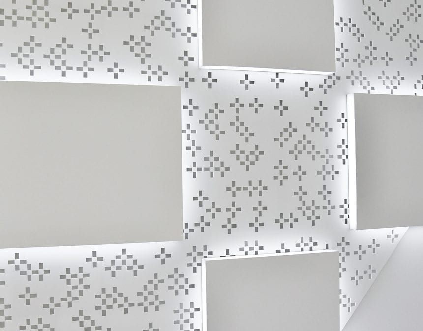 The perforated aluminum panel contains cutouts of NRG's logo in a carefully scaled and randomized manner.