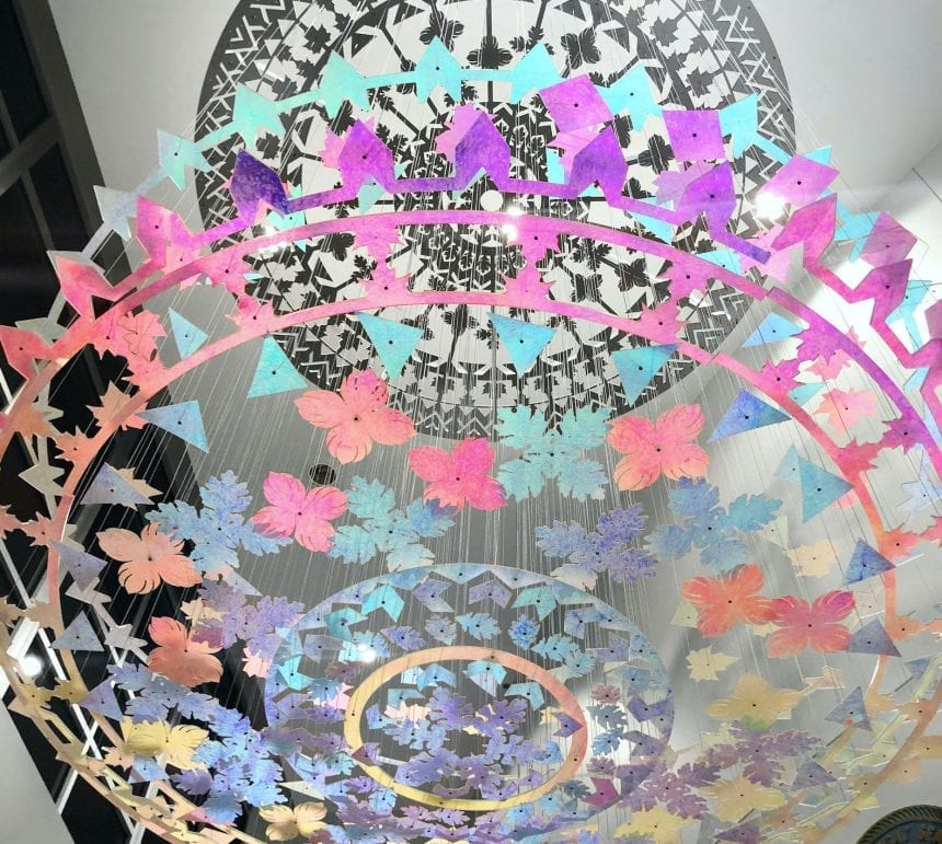 Two hundred colorful dichroic leaves and patterns hang individually from the ceiling