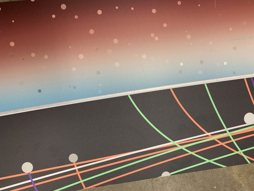 The panels were printed on a brushed aluminum composite material using transparent colors over the metal, contrasted with a rich opaque black background. The colors and exposed metal shimmers as the viewer moves through the space.