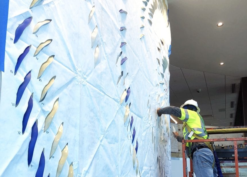 Our installation crew placing the ceramic pods on the wall at the client's site.